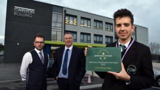 Pupil James Gibson from Year 11 holds the award given to Carlton Bolling by the World Class Schools Quality Mark flanked by Assitant Head Tony Moon and Head Adrian kneeshaw.