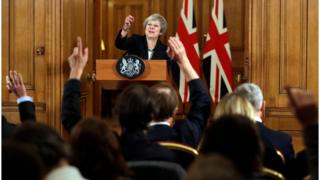 Theresa May pointing to journalists