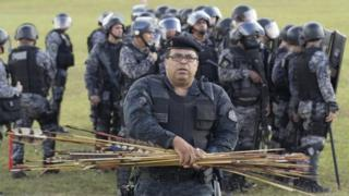 A member of the Brazilian police gathers arrows fired by Brazilian natives during a protest at Explanada dos Ministerios in Brasilia, Brazil, on 25 April 2017