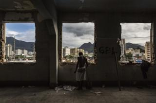 A man stands at the windows of the abandoned Ministry of Finance building (now an occupied building/squat) in the 'Favela' Mangueira community, North Zone, Rio de Janeiro, Brazil