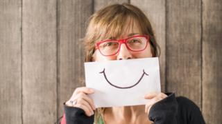 Una mujer sostiene un dibujo de una sonrisa.