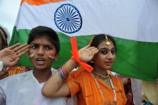 """In this photograph taken on August 30, 2012, Indian school children salute as they stand to attention and sing the national anthem """"Jana Gana Mana"""" in Hyderabad."""