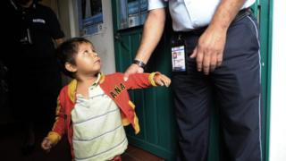 Um oficial de imigração segura pelo braço uma criança no Mexico