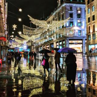Shoppers and Christmas lights reflected on a wet pavement