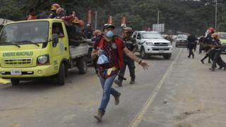 Volunteers and rescuers evacuate the disaster zone as a column of smoke and ash rises from the area where lava flowed down the Fuego Volcano,