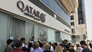 People gather outside a branch of Qatar Airways in the United Arab Emirate of Abu Dhabi on June 6, 2017