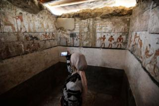 A woman takes a photo inside the tomb of an Old Kingdom priestess adorned with well-preserved and rare wall paintings on the Giza plateau in Cairo that was unveiled on February 3, 2018 after being discovered during excavation work in Giza's western cemetery by a team of Egyptian archaeologists. Antiquities Minister Khaled al-Enany told reporters the tomb belong to Hatpet, a priestess to Hathor, the goddess of fertility who assisted women in childbirth.