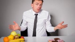 Hombre eligiendo entre frutas bollería.