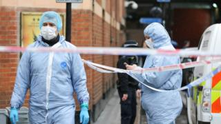 Forensic officers are seen at the crime scene outside The Coach and Horses pub in Romilly Street in Soho