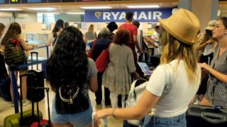 Passengers queue for a Ryanair aircraft