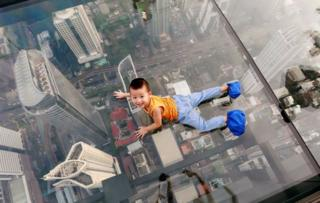 A boy plays on the glass of a skywalk in Bangkok
