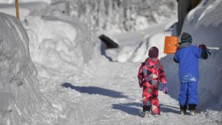 Children walk along a snow covered road in Gerold, Germany, 11 January 2019