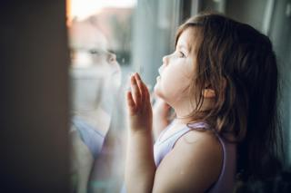 Coronavirus: A child looks out a window at the outside world