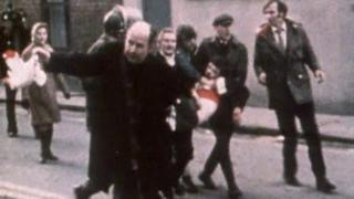 Fr Edward Daly waves a white handkerchief as Jackie Duddy is carried away on Bloody Sunday, 30 January 1972