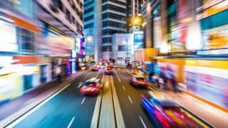 Una calle con autos circulando a alta velocidad
