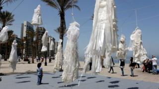 People stand next to an artwork, shows hanging wedding white dresses, to protest against article 522 in the Lebanese penal code, at Ain el Mraysseh Square, Beirut, Lebanon, 22 April 2017