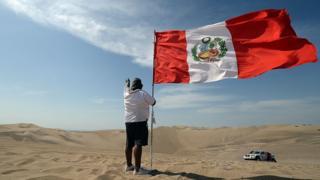 Un hombre con una bandera peruana
