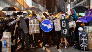 Protesters stand together with makeshift shields