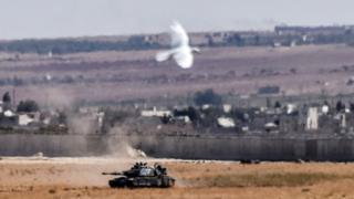 A bird flies near a Turkish tank coming from Syria during clashes between Turkish army and IS militants on September 4, 2016 at Elbeyli, in the southern region of Kilis.