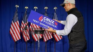 A worker for Republican presidential candidate Sen. Ted Cruz, R-Texas, removes the campaign sign from the podium following primary night campaign event in Indianapolis, Tuesday, May 3, 2016