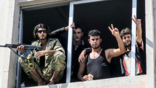 Free Syrian Army fighters gesture in Jarablus, Syria, Wednesday, Aug. 31, 2016.