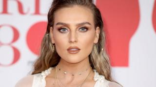 Perrie Edwards at an event, wearing makeup which covers up her freckles.