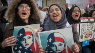 Three Muslim women protest Donald Trump's immigration order.