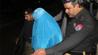 Pakistani policemen escort Afghan refugee woman Sharbat Gula (C) as she leaves the Lady Reading Hospital where she was treated, in Peshawar on November 9, 2016, before her deportation to Afghanistan.