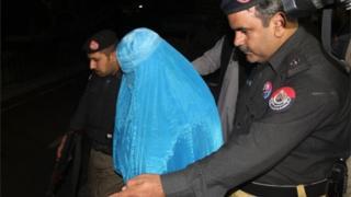 Polícia do Paquistão escolta Sharbat Gula na saída do hospital, antes de ser levada para a fronteira