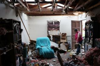 A Panama City resident begins cleaning her home, which has had the roof blown off.