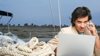 Un hombre que trabaja en su laptop entre cuerdas de navegación (de vacaciones)