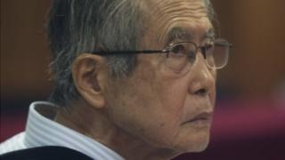 Peru's jailed, former President Alberto Fujimori, photographed through a glass window, attends his trial at a police base on the outskirts of Lima, Peru, Tuesday, June 28, 2016.