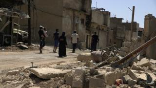 Ishar, a mother-of-four whose husband was killed by IS during the battle for Mosul, walks through the Old City with her children