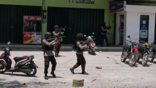 Police fire warning shots outside a shop in Palu, Indonesia