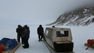Residentes del pueblo preparan un trineo para viajar.