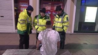 Paramedics attending a drunk man in the street