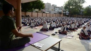 Indian school students attend a yoga workshop conducted by teachers from The Sri Sri Ravi Shankar Institute at The FD Higher Secondary School in Ahmedabad on June 16, 2015