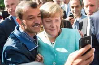 Angela Merkel poses for selfie with a man seeking asylum at a reception centre in Berlin (9 Sept)
