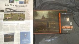 What is believed to be the missing painting is shown next to a dated copy of the New York Times and a book