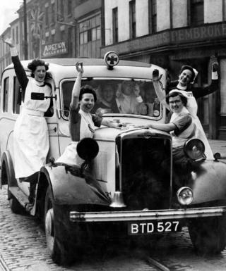 Nurses on a car waving