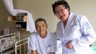Davaasuren con Renchin, un paciente en el Hospital Nacional para el Cáncer de Mongolia.