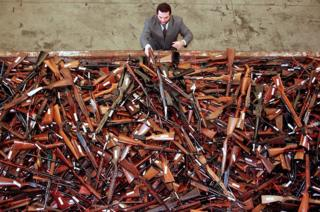 Mick Roelandts, firearms reform project manager for the New South Wales Police, looks at a pile of around 4,500 prohibited firearms that have been handed in under the Australian government's buy-back scheme in Sydney, Australia. 16 June 2017