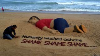 Indian artist Sudarsan Pattnaik works on a sand sculpture depicting drowned Syrian boy Alan Kurdi at Puri beach, some 65 km away from Bhubaneswar, on September 4, 2015.