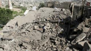 A man walks on the rubble of houses destroyed by Saudi-led air strikes in Taiz on 21 August 2015