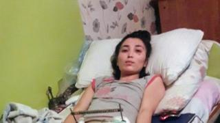 Saina Raisova on the bed after she was discharged from the hospital