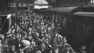 Child evacuees queuing at a train station waiting to board trains so they can leave London.
