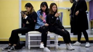 women looking at phones