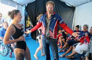 Prince Harry tries on USA Invictus Team Member Elizabeth Marks's Team USA jersey