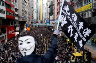 A protester wearing a Guy Fawkes mask waves a flag during a Human Rights Day march, organised by the Civil Human Rights Front, in Hong Kong, 8 December 2019.