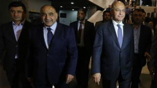 Iraq's Prime Minister-designate Adel Abdul Mahdi (2nd Left) and Barham Saleh (2nd Right) walk out of the Iraqi parliament on 2 October 2018